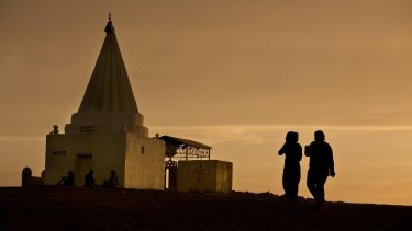 Women visit a Yazidi shrine overlooking at Kankhe Camp for the internally displaced in Dahuk, northern Iraq.