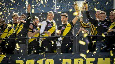 Giant killers: Richmond players and coach Damien Hardwick present the 2019 premiership cup to the Tiger faithful.