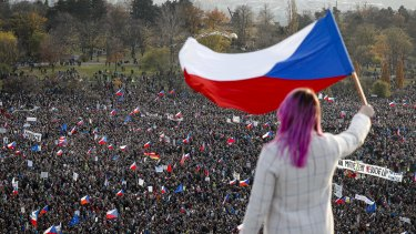 Days earlier, a woman waves a Czech flag from a roof as people take part in a large anti-government protest in Prague.