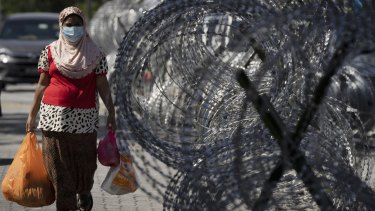 A woman walks home with groceries next to barbed wire in the locked-down area of Selayang Baru in Kuala Lumpur, Malaysia.