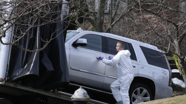 Crime scene investigators load a car that appears to have been checked for fingerprints onto a truck outside Cali's home.