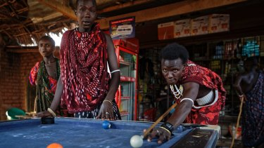 Young Maasai men relax and play a game of pool at a bar by the side of the road in the late afternoon at Mkata junction, near Mikumi National Park.