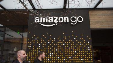 Pedestrians walk past the Amazon Go store in Seattle, Washington.