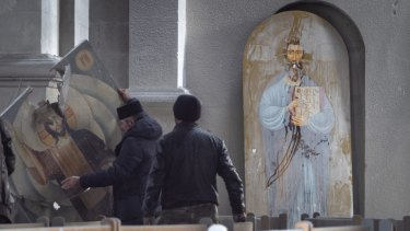 Men lift an icon in the Holy Saviour Cathedral damaged by shelling during a military conflict, in Shushi, in the self-proclaimed Republic of Nagorno-Karabakh.