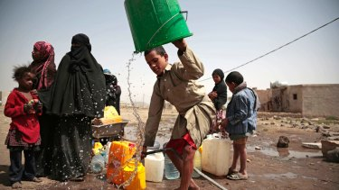 A boy rinses a bucket as he and others collect water in war-torn Yemen.