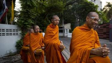 Buddhist monks wear face shields while collecting alms during a partial lockdown in Bangkok on Monday.