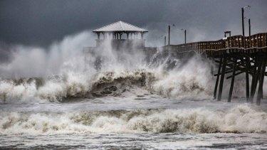 Waves slam the Pier House Restaurant in Atlantic Beach, NC, on Thursday.