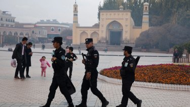 Security personnel on patrol outside a mosque frequented by Uighurs in Xinjiang.