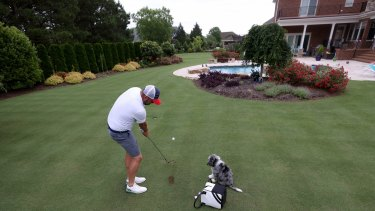 Marc Leishman hits the ball to the green in his backyard while his dog Doc looks on in Virginia Beach.