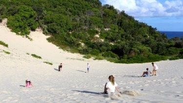 Tourists sandboarding on North Stradbroke Island.