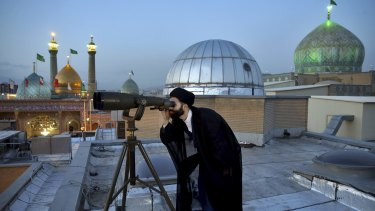 A cleric looks through binoculars to sight the new moon that signals the start of the Islamic holy fasting month of Ramadan at the shrine of the Shiite Saint Imam Abdulazim.