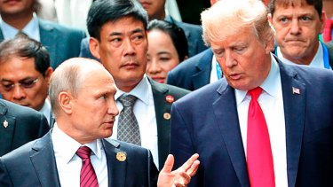 US President Donald Trump, right, and Russia President Vladimir Putin talk during the family photo session at the APEC Summit in Danang last year.