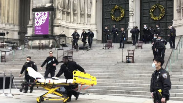 Emergency medical personnel pull a stretcher up to the scene of the shooting at the Cathedral Church of St John the Divine in New York.