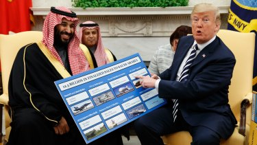 March 2018: President Trump holds a chart highlighting $US12.5 billion in arms sales to Saudi Arabia during a meeting with Saudi Crown Prince Mohammed bin Salman in the Oval Office.