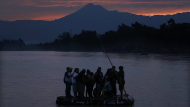 Central American migrants stand on a raft to cross the Suchiate River from Guatemala to Mexico, with the Tacana volcano in the background, near Ciudad Hidalgo, Mexico.