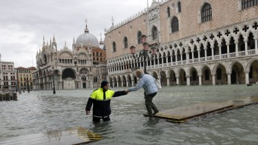 A city worker helps a woman who decided to cross St. Mark square on a gangway, in flooded Venice last month.