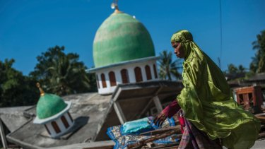 A Muslim woman walks past a mosque collapsed during the August 9 earthquake in Gangga, Lombok Island.