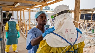 A health care worker prepares a colleague's protective gear at an Ebola virus clinic in Sierra Leone in 2015.