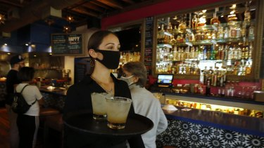 A masked waitress serves drinks in a bar in California.