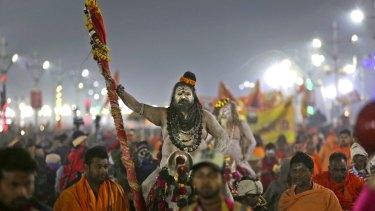 Naked ash-smeared Naga Sadhus or Hindu holy men arrive for a dip.