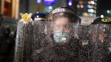 A police officer has a flower placed on his riot shield by a protester in Bristol, England.