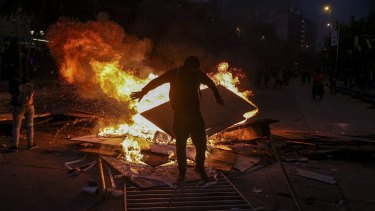 A wet anti-government protester dries his clothes by standing close to a burning street barricade in Santiago, Chile.