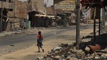 A girl walks across a street surrounded by debris and destroyed buildings in West Mosul after fleeing Islamic State in June 2017.