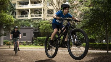 A group of kids having fun jumping their bikes in Rushcutters Bay Park.