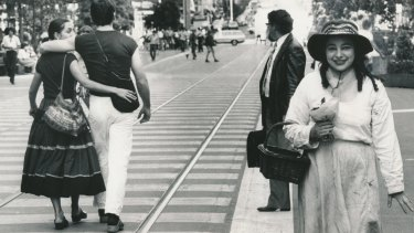 Mirka Mora, in paint-spattered clothes, walks along the Bourke Street Mall, 1981.