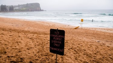 A sign on Avalon Beach asking the public not to congregate on the beach due to the COVID outbreak.