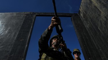 Private Brodie Smith (right)  observes a Filipino marine as he enters a mock building during training.