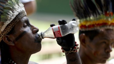 A representative of the Huitoto and Ticuna indigenous communities drinks Coke in Leticia, on Colombia's Amazon river border with Brazil and Peru. A doctor working with the Ticunas has tested positive for coronavirus.