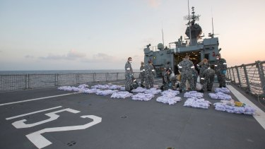 Crew members of HMAS Warramunga lay parcels of seized heroin on the flight deck of the ship during an operation in the Western Indian Ocean, seizing 915kg of heroin valued at more than AUD$274 million in January 2018.