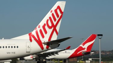 The Virgin Australia Holdings Ltd. logo, left, and Qantas Airways Ltd. logo are displayed on the tails of aircraft at Sydney Airport in Sydney, Australia, on Monday, Feb. 8, 2016. Virgin Australia is scheduled to announce half-year earnings on Feb. 11. Photographer: Brendon Thorne/Bloomberg