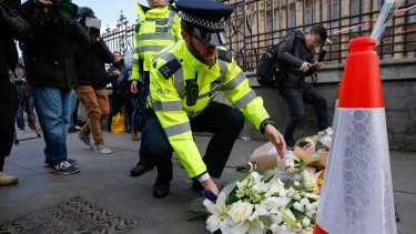 A police officer lays flowers as he pays his respects to victims of a terror attack outside the Houses of Parliament in London last year.
