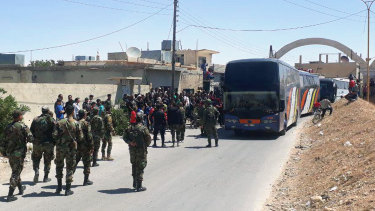 This photo released by the Syrian official news agency SANA, shows Syrian government forces overseeing the evacuation by bus of rebels and their family from the towns of Ruhaiba in the eastern Qalamoun region in the Damascus countryside.