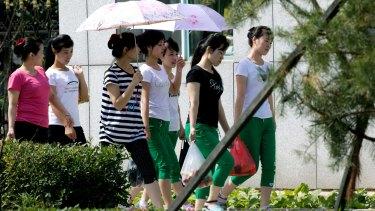 North Korean workers walk into the Hong Chao Zhi Yi garment factory in Hunchun in north-eastern China's Jilin province near the Russian border.