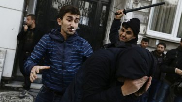 A man in plain clothes, left, and a uniformed security officer beat a protester demanding freedom for detained  MPs of the pro-Kurdish People's Democratic Party  in Istanbul in 2016.