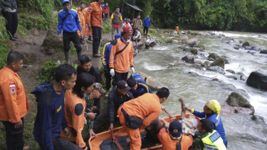 Rescuers remove the body of a victim of a bus accident in Pagaralam, Indonesia, on Tuesday.