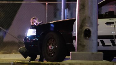 A police officer takes cover behind a police vehicle during a shooting near the Mandalay Bay resort and casino on the Las Vegas Strip on October 1, 2017.