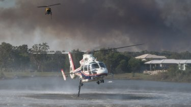 Helicopters take on water to water-bomb the Sunshine Coast bushfires.