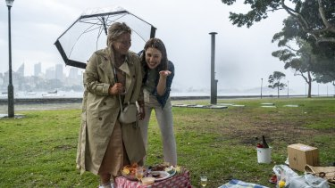 A picnic is disrupted due to heavy rain at Rushcutters Bay.