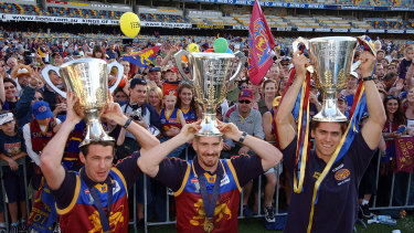 Jason Akermanis (centre) celebrates three grand final wins by the Brisbane Lions.