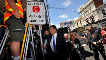 Then-Premier Ted Baillieu replaces the old clearway sign with a new sign to restore the original clearway times after winning the 2010 election. Traders pop open the champagne.