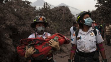 A firefighter carries the body of a child recovered near the Volcan de Fuego, in Escuintla, Guatemala.