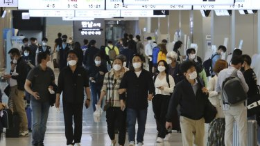 People wearing face masks arrive at the domestic flight terminal of Gimpo airport in Seoul, South Korea in May.