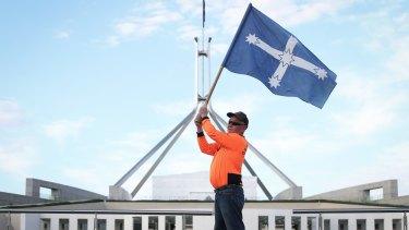 A CFMMEU representative flies the Eureka flag in front of Parliament House.