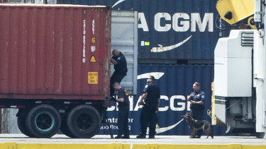 Authorities search a container along the Delaware River in Philadelphia.