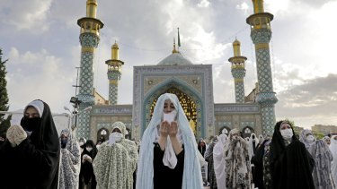 Worshippers wearing protective face masks offer Eid al-Fitr prayers outside a shrine to help prevent the spread of the coronavirus, in Tehran in May.