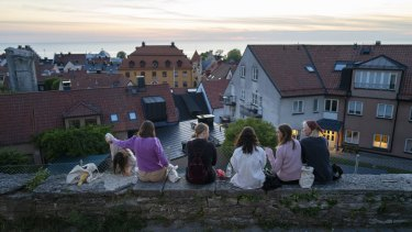 Limited to groups of eight: people sit along a street in the town of Visby in Gotland, Sweden.